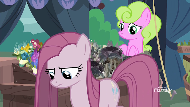 Pinkie grayed out with straight hanging hair in Pinkamena form whose aura is killing nearby flowers in a stall.