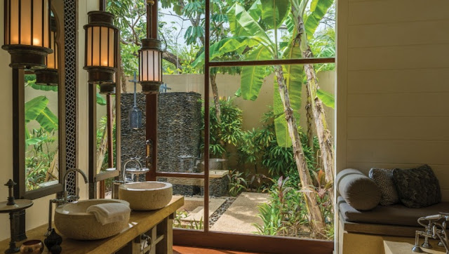 Los baños de visitas del Four Seasons Resort Langkawi en Malasia cuentan con enormes arcos, brillantes tragaluces y tinas al aire libre en jardines privados