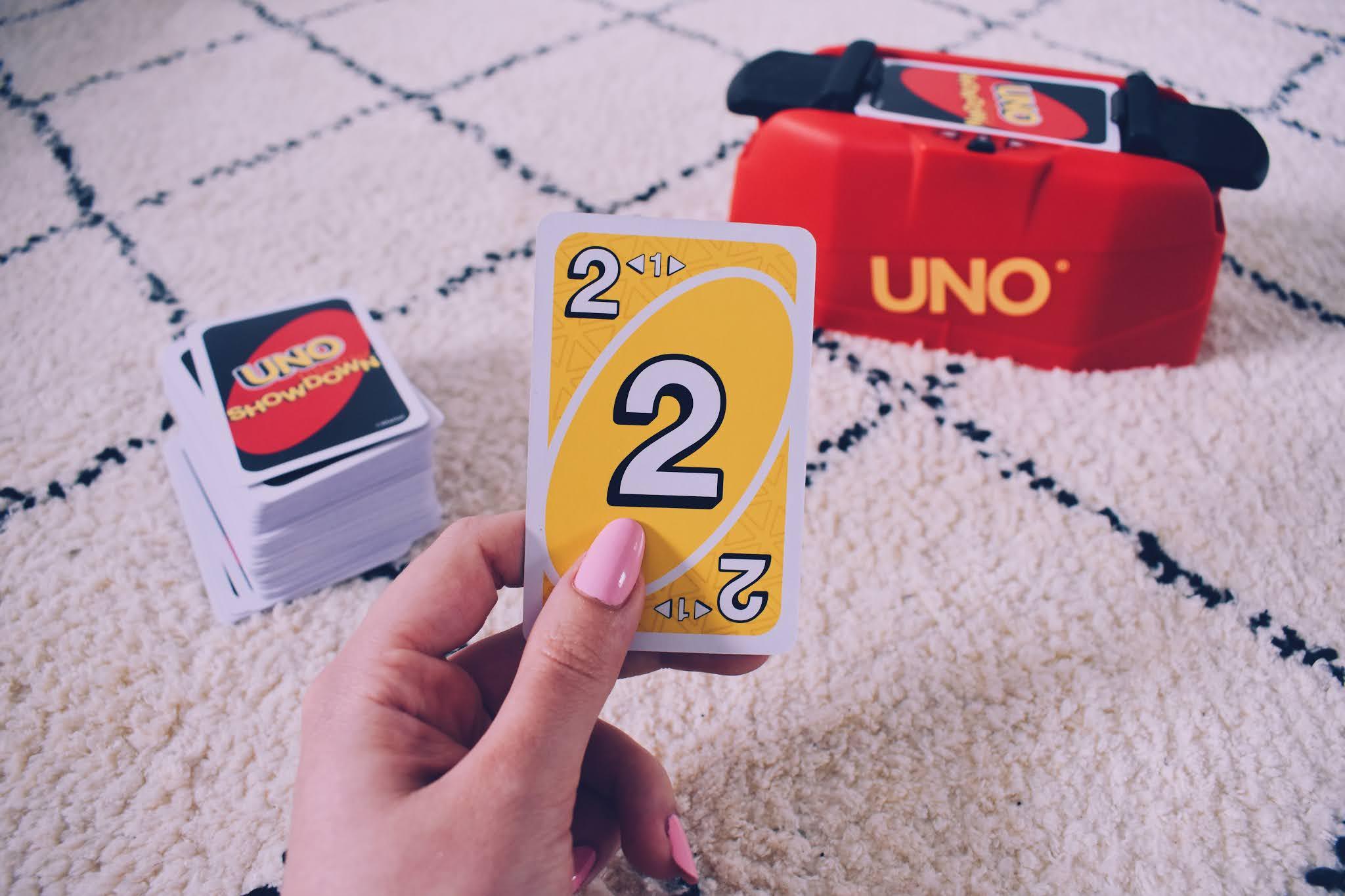 UNO Showdown-unit en aflegstapel uitgestald op een witte mat op de achtergrond en een hand die een gele showdown kaart vasthoudt op de voorgrond.