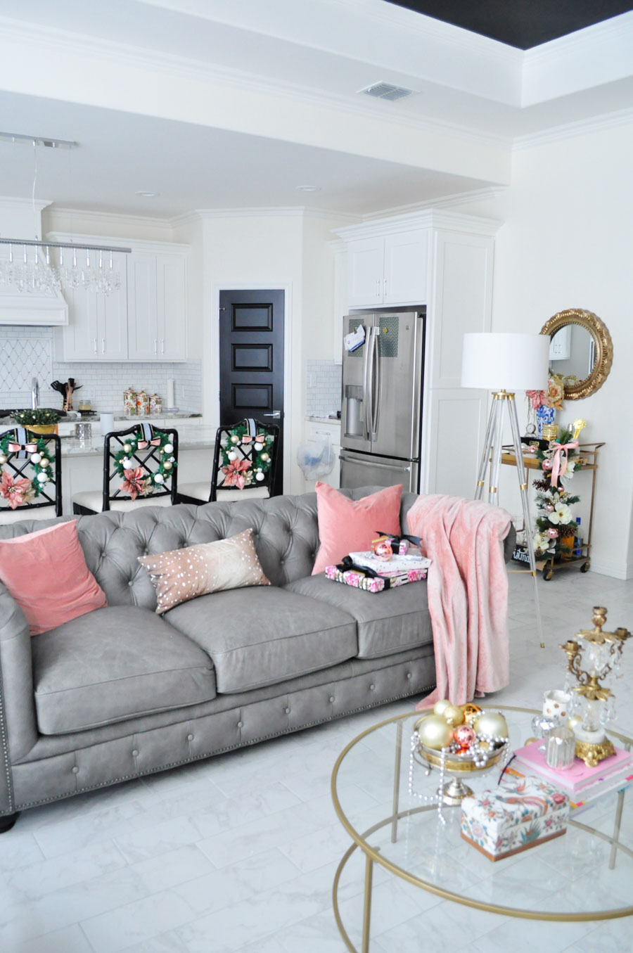 Open concept living, kitchen and dining space decorated for the holidays in blush, silver, white and gold. Love the gray chesterfield and crystal chandeliers!