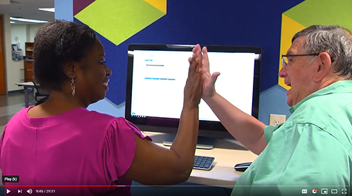 snapshot from video featuring Rio Salado's Faculty Chair of Mathematics John Jensen working with student Shawnda Howerton. They're at a computer giving each other a high-five