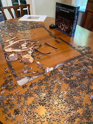 Puzzle pieces spread out on a table with a partially completed puzzle in the middle. There is a frame mat wrapped in plastic on the edge of the table.