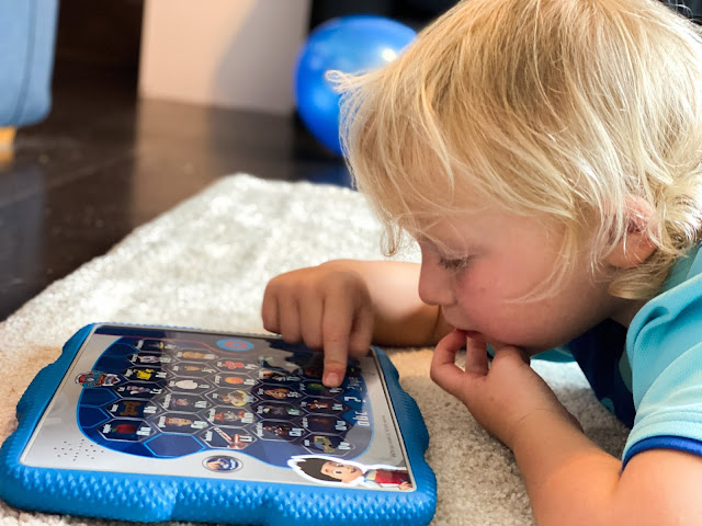 a child lying on the floor pressing buttons on a toy tablet which is teaching phonics using the PAW patrol characters