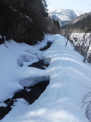 道の上を雪解け水が流れて、沢状態になっている平沢林道