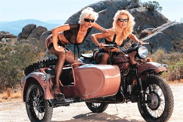 Two platinum blonde girls in lingerie aboard a Ural sidecar.