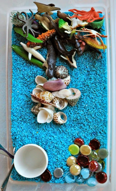 Blue rice ocean sensory bin, including sea glass, shells, and plastic ocean animals
