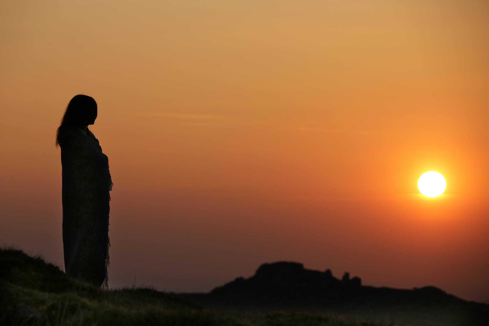 Girl staring at a sunset over Dartmoor