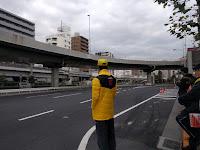 国道15号線と黄色い帽子とジャンパーを着たボランティアの人