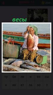 сидит девушка продавец с весами и продает рыбу