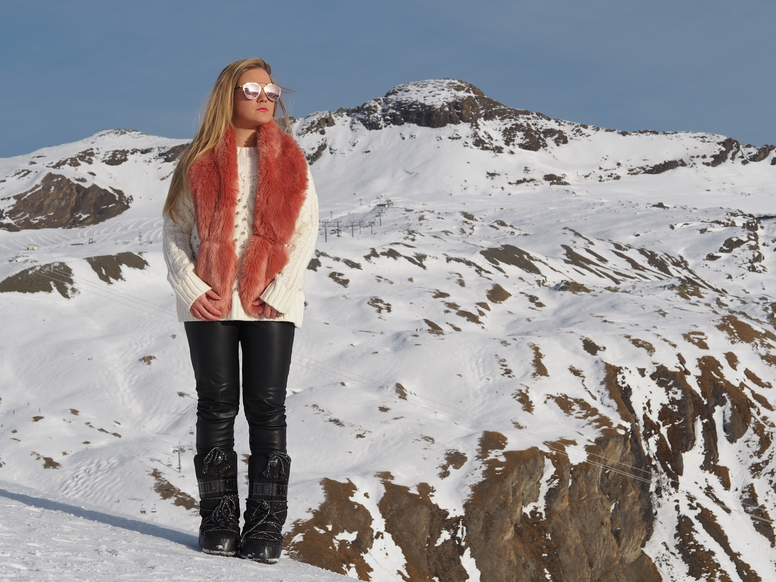 Blonde girl sitting in snowy mountains wearing blue and pink fur, sunglasses and moon boots, Val d'Isere, France
