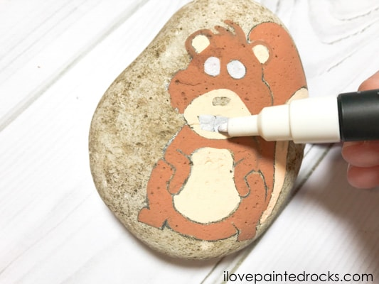 painting the eyes and teeth of the squirrel painted rock