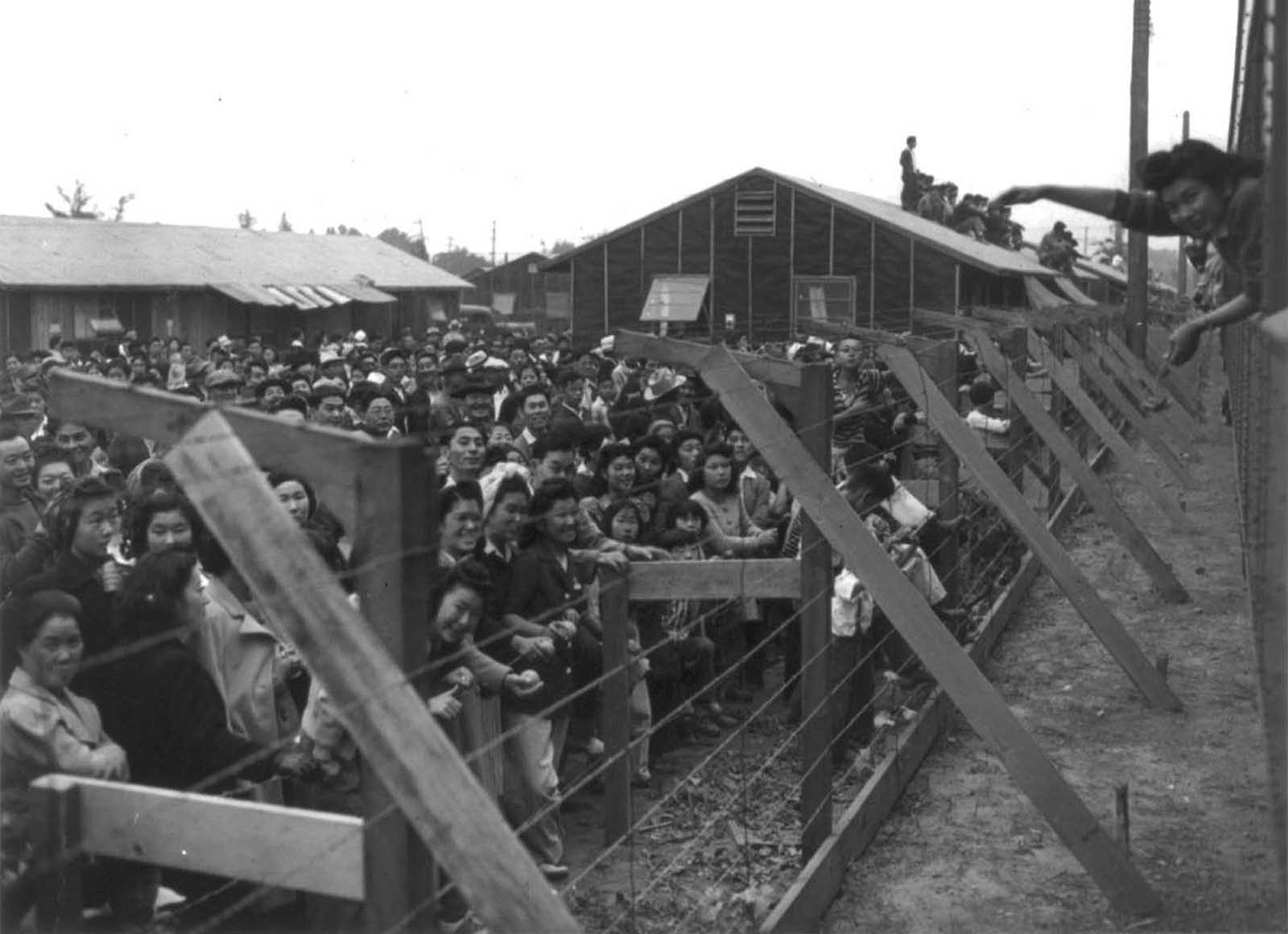 A crowd of Japanese Americans stand behind a barbed wire fence waving to departing friends on train leaving Santa Anita, California.