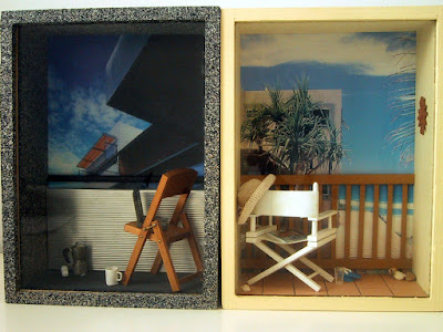 Two one-twelfth scale modern miniature balcony scenes in box frames. On the left is a city balcony, with sprayed concrete walls and floor and a corrugated iron balcony wall. On the balcony is a folding wooden chair with a laptop on it. On the floor is a cordless phone, a mug and a stovetop espresso jug. On the beach balcony is a white director's chair with a woven hat on the back, a magazine on the seat, and a pair of jandals and a glass on the floor. The balcony overlooks the sea and some cabbage trees.
