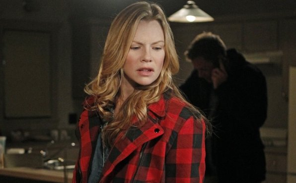 NCIS - EJ (Sarah Jane Morris) dressed in black and red flannel jacket stands in foreground in kitchen, DiNozzo (Michael Weatherly) in background makes a phone call