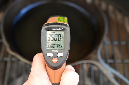 temp checking cast iron skillet using a non-contact thermometer.