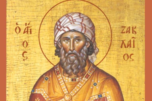 A imagem mostra uma representação de zaqueu, o publicano. Com barba grande, uma túnica branca com listras vermelhas enrolada na cabeça com uma grande auréola sobre sua cabeça.