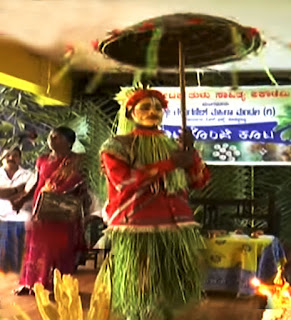 Aati Kalenja with a rotating umbrella in his hand performs in Mangalore city