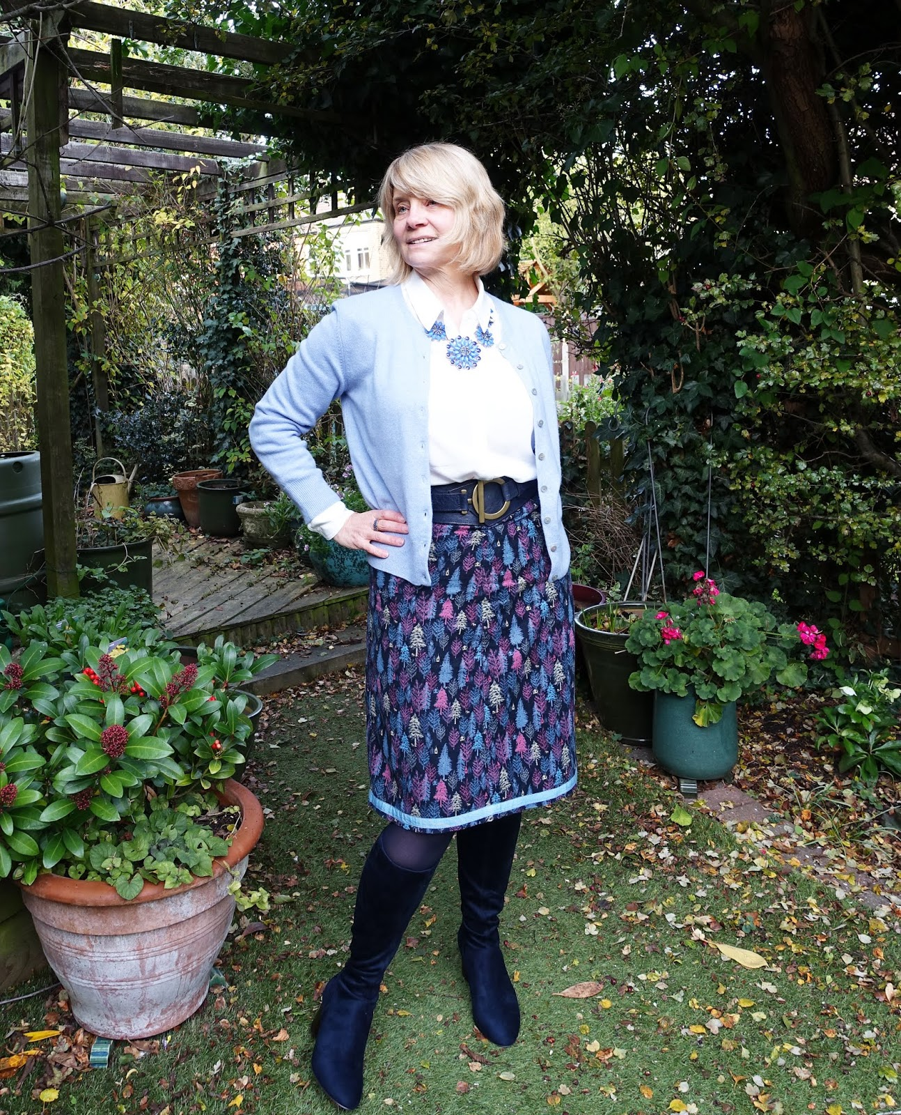 Over 50s style blogger Is This Mutton transforms a skirt and cardigan by adding long boots, a necklace and a wide belt