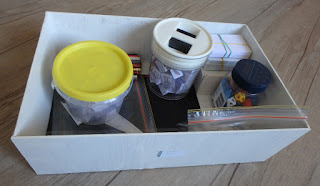 White box on wooden floor filled with containers of game supplies