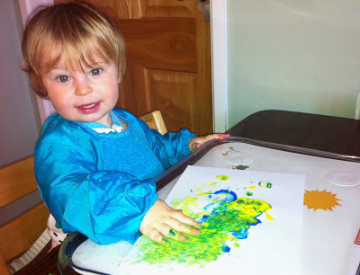 Child looking at camera - painting a picture in blue and yellow using hands