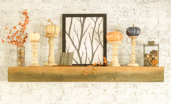 fall mantel with pumpkins and branches