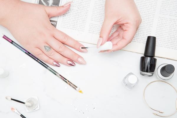 Manicure mãos femininas passando esmalte nas unhas