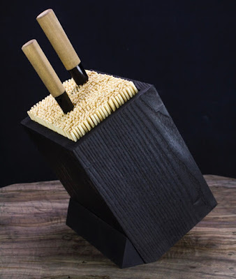 knife block made of a dark wood with lots of light-colored bamboo skewers inside