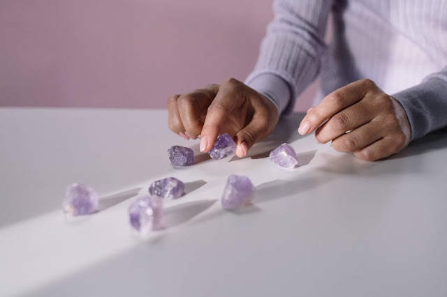 Close up of a person's hand while they are counting purple gemstones.