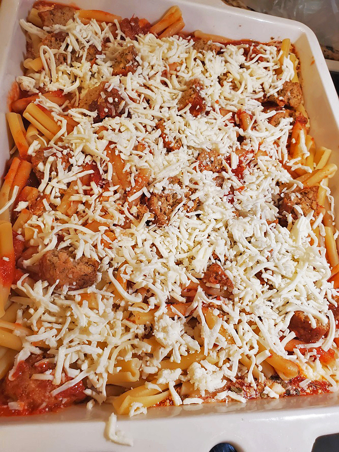 this is baked cavatelli with sausage and shredded cheese on top