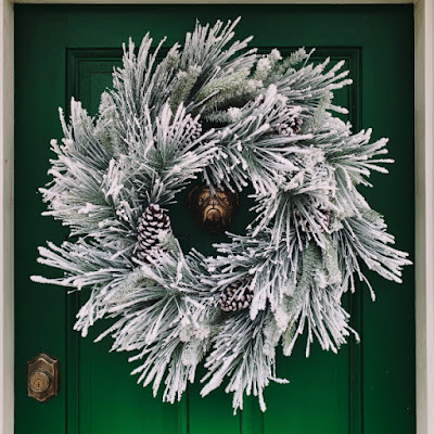 Front door with ice colored wreath