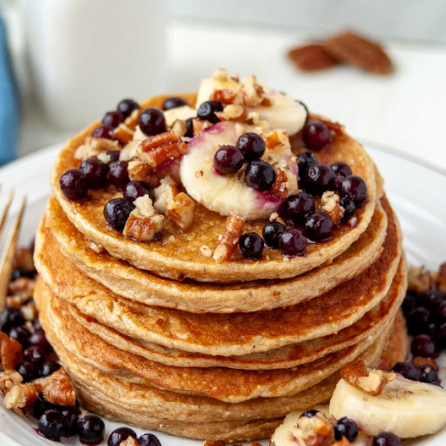close stack of golden pancakes topped with blueberries, bananas and pecans