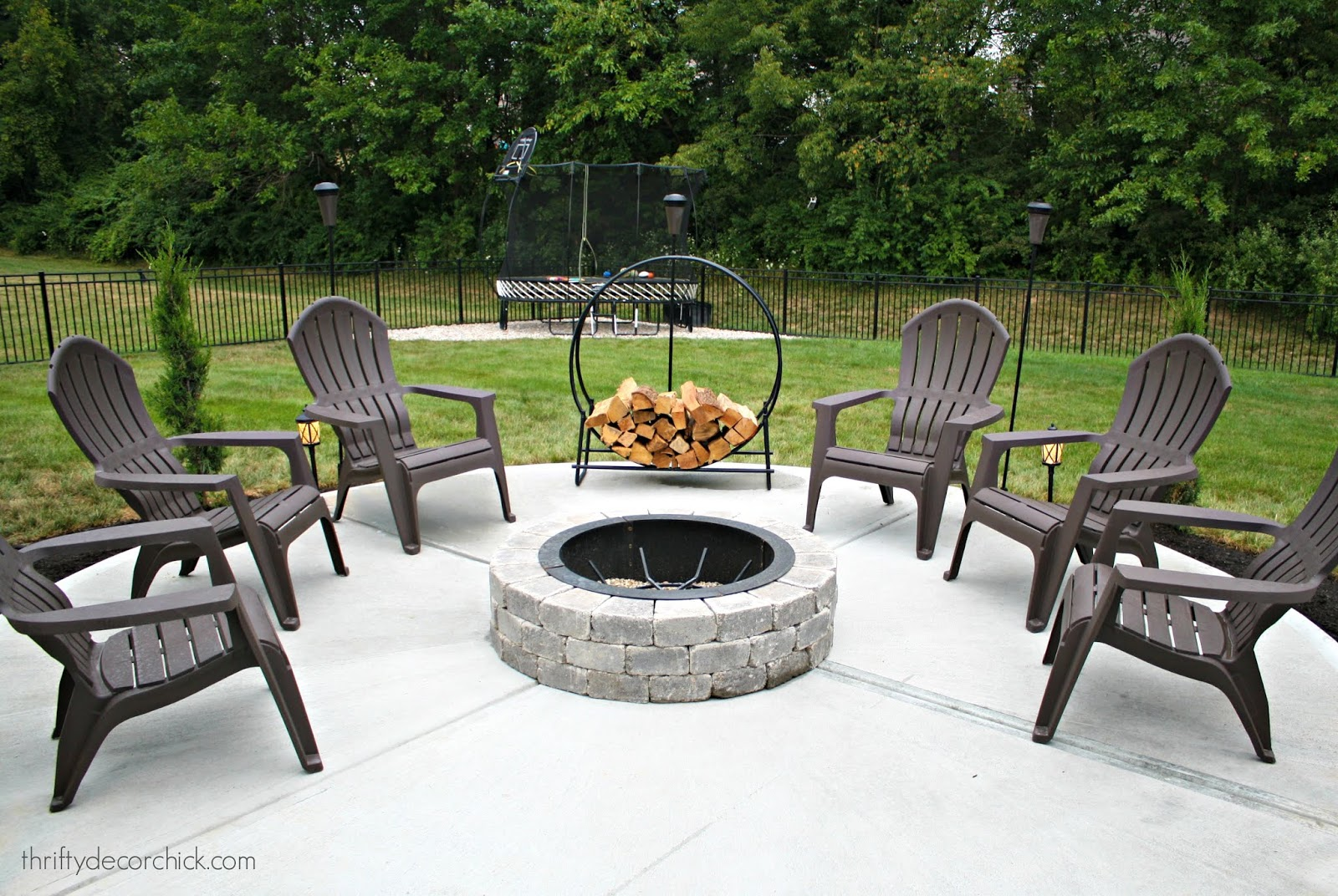 Round fire pit on patio with Adirondack chairs