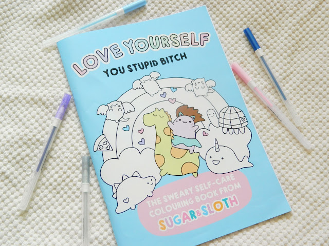 A photo of a colouring book featuring an illustration of cute animals surrounding a rainbow. The background is bright blue.