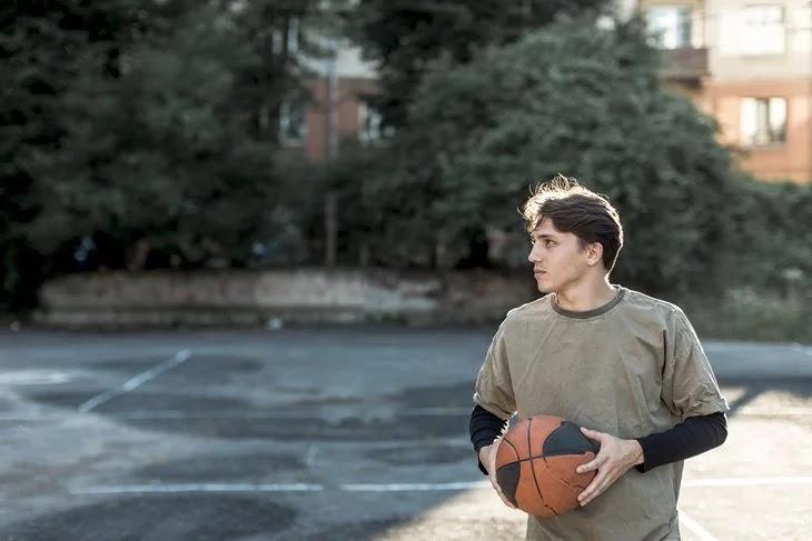 Homem segurando uma bola de basquete