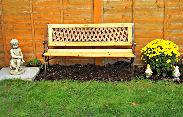 A memorial bench, flanked by a large yellow Chrysanthemum and a stone cherub.