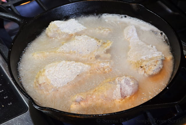 Extra Crispy Fried Chicken frying in a Cast Iron Pan.