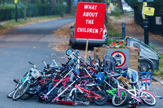 """A pile of dozens of children's bicycles in one of Ealing's Low Traffic Neighbourhoods with a sign saying """"What about the Children?"""""""