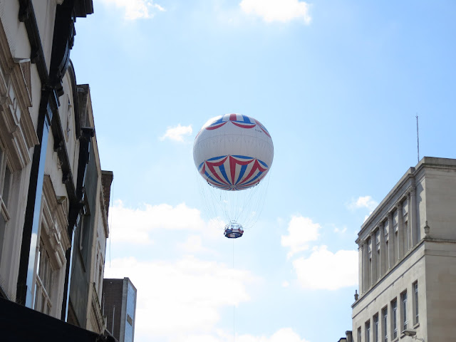White passenger balloon with red and white patterns, basket below, abpve city street.