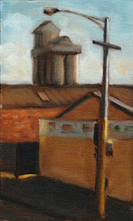 Oil painting of a traffic pole and lights in front of light industrial buildings with distant silos.