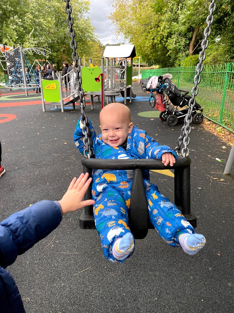 8 month old baby boy being pushed in a swing