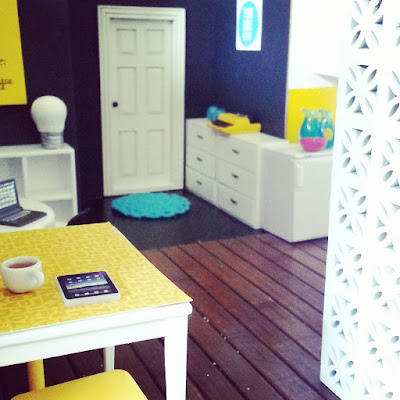 One-twelfth scale modern miniature co-working space with a high table, round table, storage and kitchen area and screen made of breeze blocks.