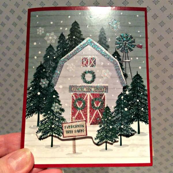 snowy barn scene on glittery Christmas card