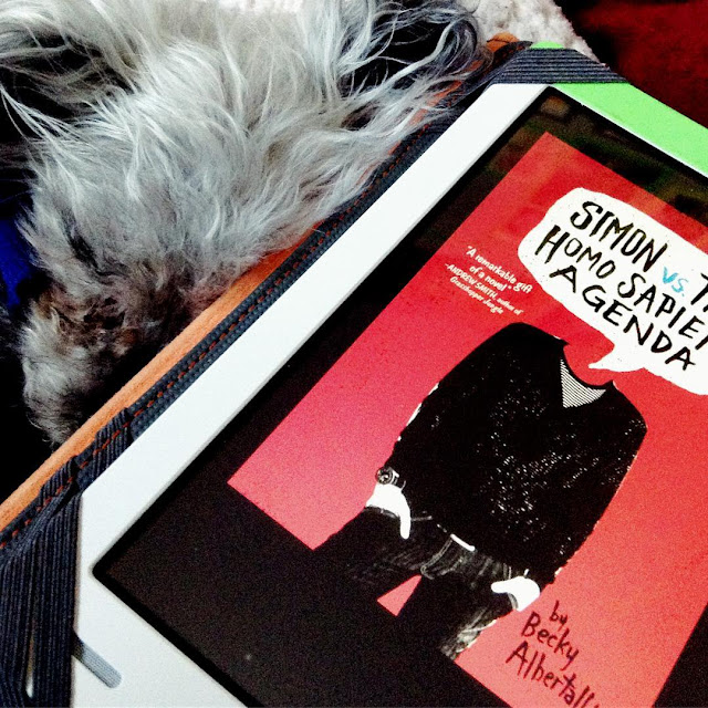 Murchie curls up tight beside a white Kobo with the cover of Simon Vs the Homo Sapiens Agenda on it. The red cover features a black-clad boy with his hands in his pockets. A speech bubble with the title on it appears in the place of his head.