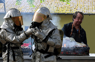 Men in fire suits in front of barbeque