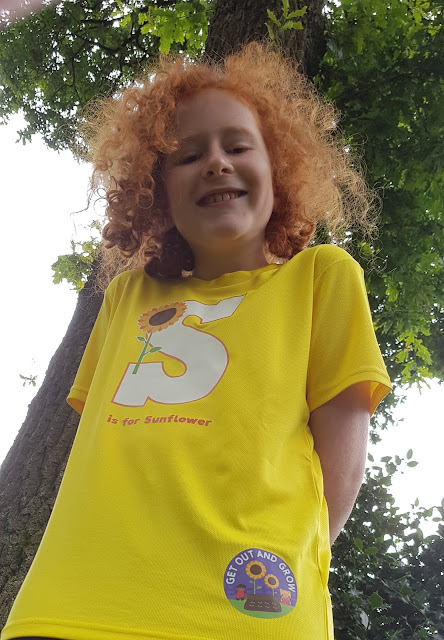 Photo of 10 year old boy in front of huge oak tree with sunflower t-shirt