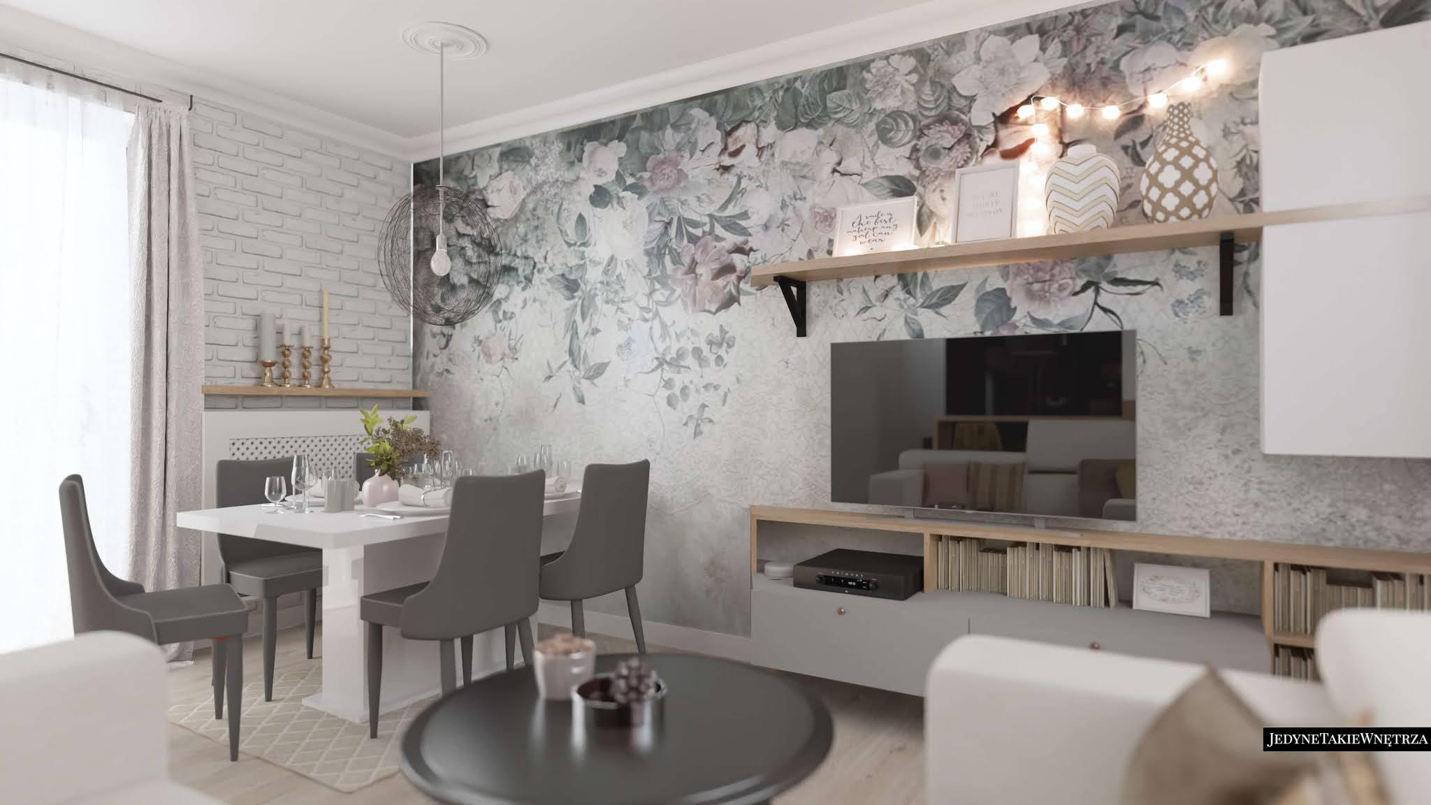 Przytulny salon, w którym stoi nowoczesny biały stół jadalniany. Ścianę zdobi romantyczna szara tapeta i listwy przysufitowe.