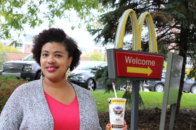 a woman standing next to a McDonald's sign