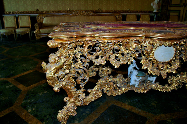 poltrone dorate, poltrone antiche, divano antico, tavolo decorato dorato, pavimenti verdi, camera