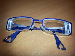 Unas gafas con montura azul y las patillas recogidas sobre un fondo de madera