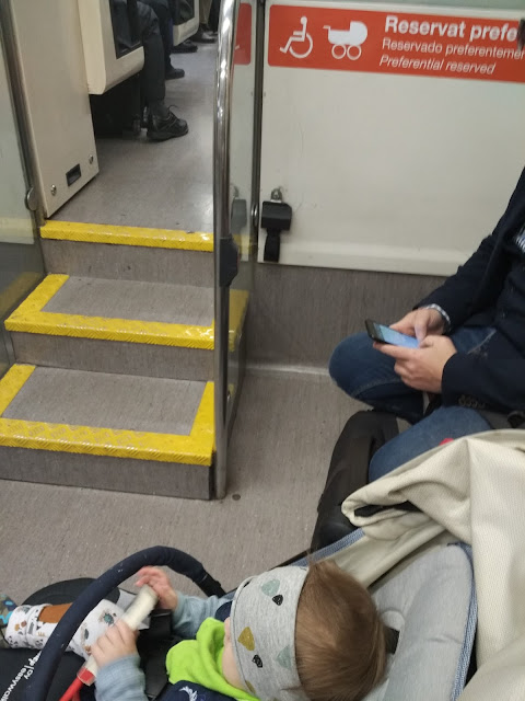 Una bebé en su carrito al lado un hombre mirando su móvil sentando debajo del cartel que informa que ese espacio está reservado para los acompañantes de personas en silla de ruedas o carritos de bebé